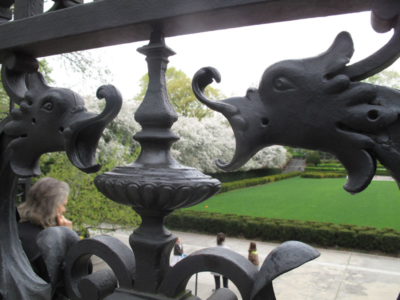 The wrought iron gate's Gargoyles fiercely guard the beauty.